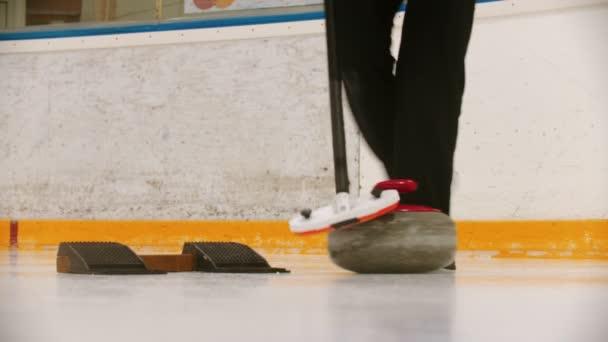 Curling - ženská ruka se odtlačí od stojanu žulovým kamenem