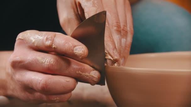 Töpferei - der Meister hilft mit einem speziellen Spachtel, die Oberfläche der Tonschale zu glätten