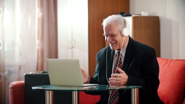 Elderly grandfather - old grandfather in headphones smiling and looking at laptop screen in his rooom