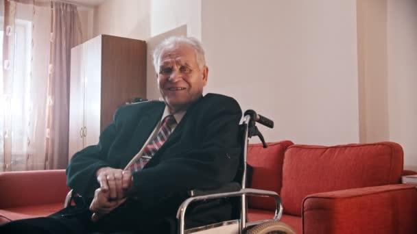 Idős nagyapa - mosolygós nagyapa tolószékben ül és a kamerába néz