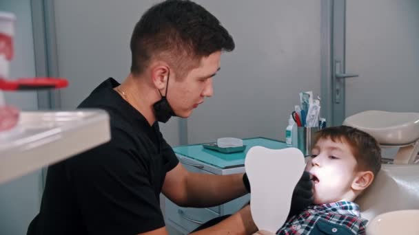 A little boy having a treatment in the dentistry - model of the human jaw on the foreground