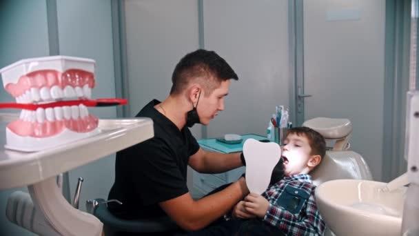 Malý chlapec s kontrolou stavu zubů v zubním lékařství - model čelisti v popředí