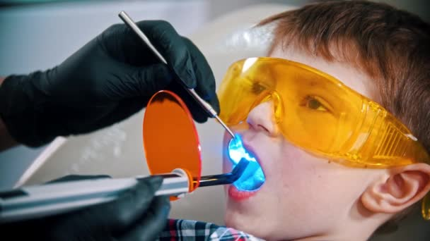 A little boy in protective glasses having his teeth done - photopolymer lamp in the mouth