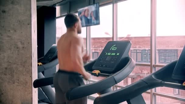 Hemdlos attraktiver Mann Bodybuilder läuft auf dem Laufband