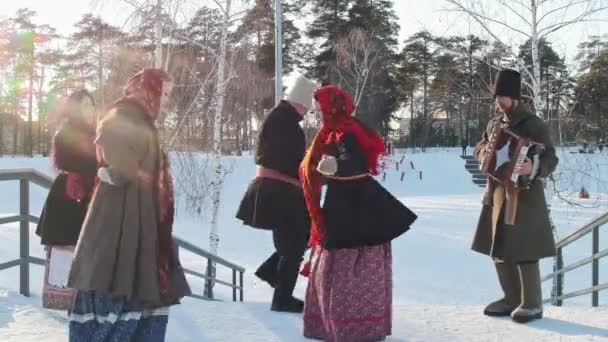 Russian folk - men and women in traditional Russian clothes are dancing to the accordion n the park