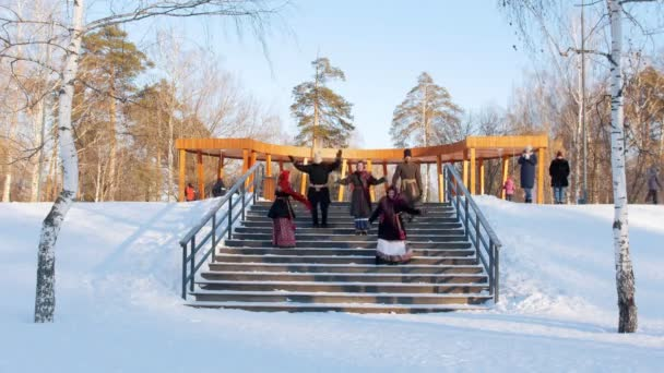 Russian folk - women in bright scarves are dance with men on the stairs