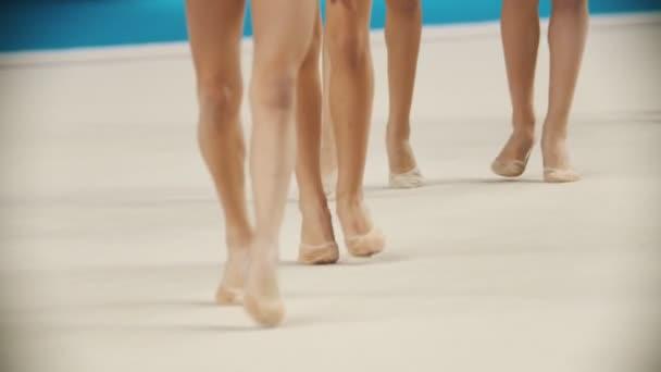 Fiatal női lábak a ritmikus torna versenyeken, ahogy kisétálnak a színpadra pointe cipőben.