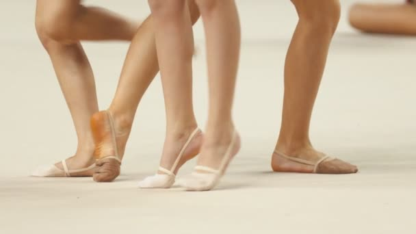 Young women legs at the rhythmic gymnastics tournaments warming up on the stage - wearing pointe shoes