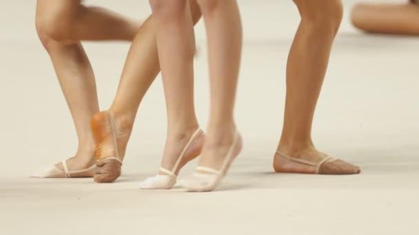 Fiatal női lábak a ritmikus torna versenyeken bemelegítés a színpadon - pointe cipőben