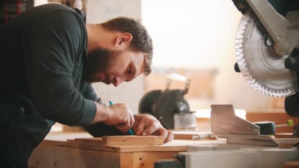 Tesařská práce - vousatý muž dělá značky na překližce