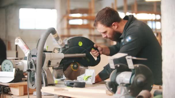 Tesařský průmysl - muž pracující v dílně u stolu s kruhovou pilou