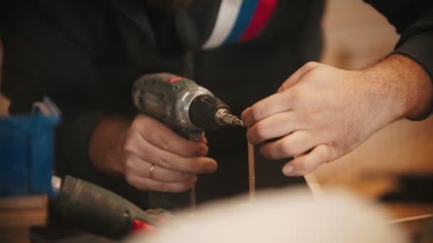 tesařská práce - muž dělník vrtání otvory v překližce v dílně