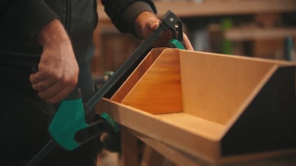 Tesařská práce - ruce dělníka, který vyrábí dřevěný organizátor