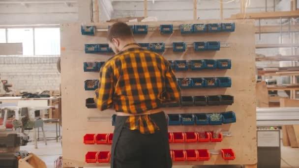 Tesařský průmysl - pracovník vybírající šrouby ze stojanu a odchází