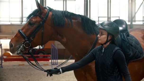 Junge Reiterin steht neben ihrem Pferd und hält die Zügel in der Hand