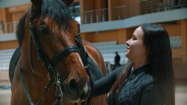 Hippodrome - fiatal lovas nő áll a lovával és mosolyog