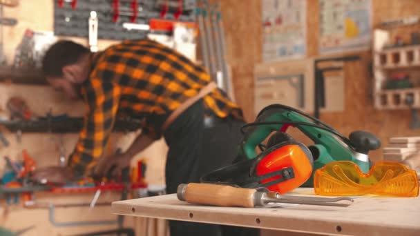 Vousatý muž pracovník ve žluté košili výběru nástrojů v dílně a vezme sluchátka ze stolu