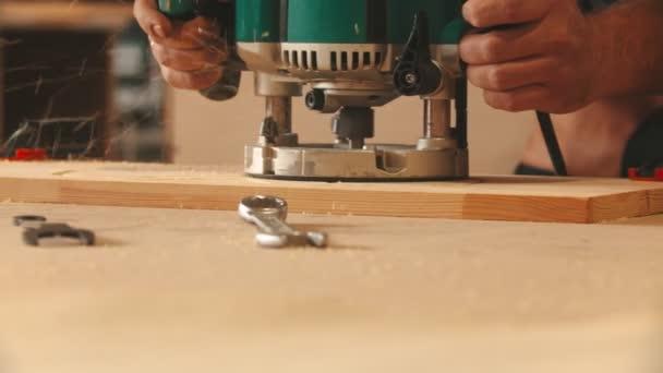 Tesařský průmysl - muž dělník v ochranných brýlích a sluchátkách vyřezává vzory z dřevěné desky