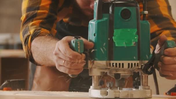 Tesařský průmysl - vousatý pracovník v ochranných brýlích a sluchátkách vyřezává vzory z dřevěného prkna