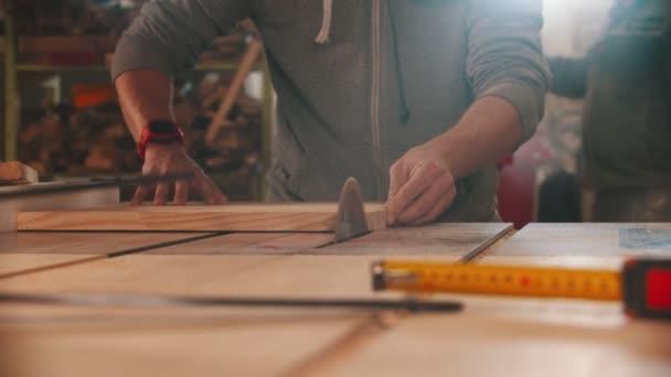 Tesařský průmysl - muž řezání malý kus dřeva pomocí velké kruhové pily