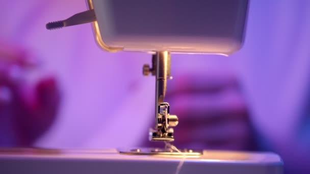 Šicí stroj - mladá švadlena dělá něco na pozadí