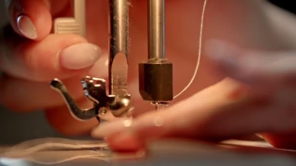 Schneiderhände fixieren die Nadelposition einer Nähmaschine