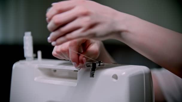 Hand der Näherin legt einen Faden an die Nähmaschine