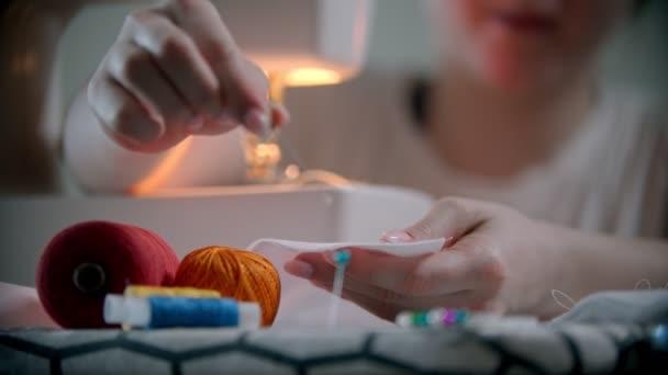 Junge Designerin steckt Stecknadeln ins weiße Tuch