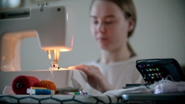 Junge Designerin näht mit einer Nähmaschine eine weiße Mehrwegschutzmaske