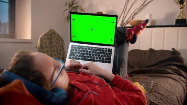 Mladík ležící na posteli s laptopem a pojídající pípnutí - zelená obrazovka