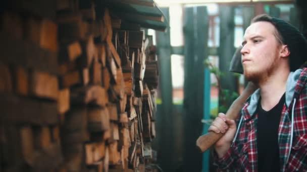 Junger Mann legt Baumstämme mit anderen Stämmen auf den Ständer
