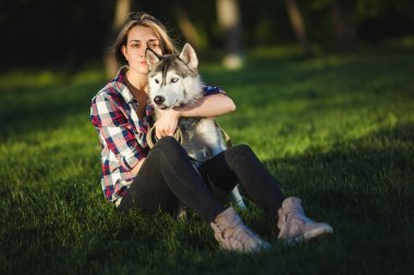 Beautiful young woman is walking with a husky dog with heterochromia