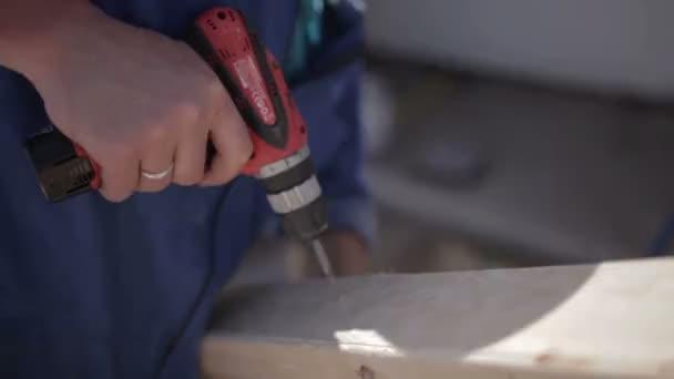 Muž pomocí ocelového vrtáku a obvyklé šroubovák na dřevěné desce