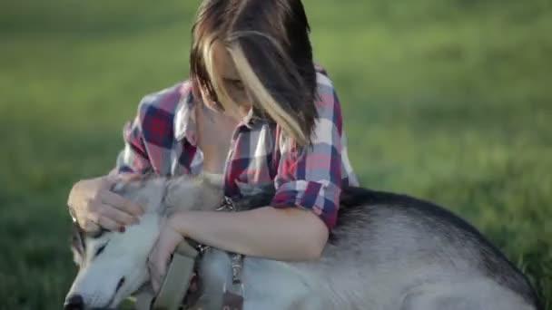 Bella giovane donna che gioca con il cane husky divertente attività allaperto