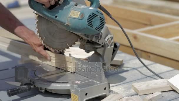 Muž pracovitý řezání dřevěné podlahové elektrické viděl v práci