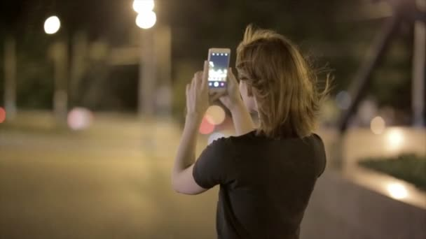 krásná mladá žena vyfotit na smartphone v noci ulice