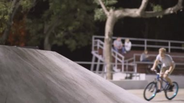MTB bicycle rider does various tricks while riding in skatepark . Extreme Sports, rider does tabletop trick at night