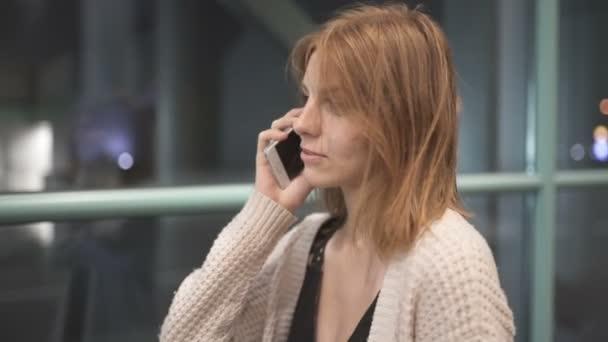 Schöne rothaarige Frau mit Smartphone-Technologie in den Stadtstraßen in der Nacht