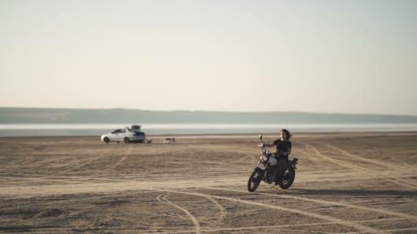 krásná mladá žena na koni starých motocyklů café racer a dělá trik. v poušti při západu slunce nebo východu slunce. Ženské cyklistiky. Zpomalený pohyb