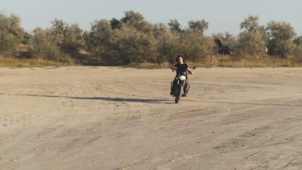 krásná mladá žena na koni starých motocyklů café racer na poušti při západu slunce nebo východu slunce. Ženské cyklistiky. Zpomalený pohyb