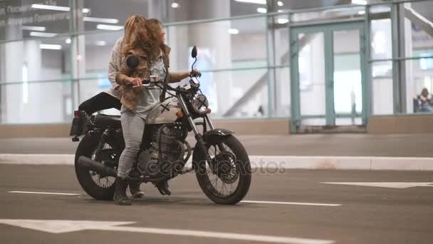 krásná mladá žena motocyklista se svou přítelkyní na motocyklu v městě noci na osvětlené ulice. Dvě ženy na kole