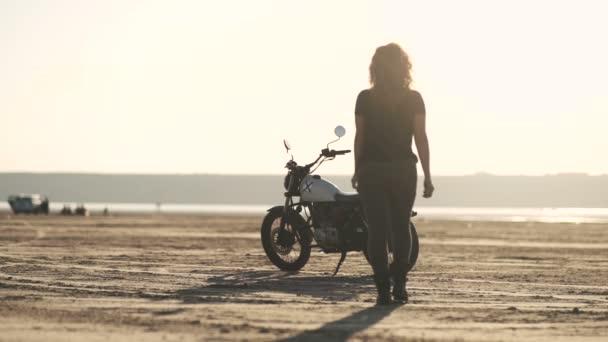 Atraktivní krásná žena jde do její staré motocyklů café racer, na něm sedí a jezdí dál. Ženské motocyklový závodník. Zpomalený pohyb