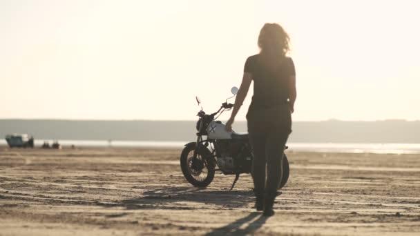 Atraktivní krásná žena jde do její staré motocyklů café racer, na něm sedí a jezdí dál. Ženské motocyklový závodník.