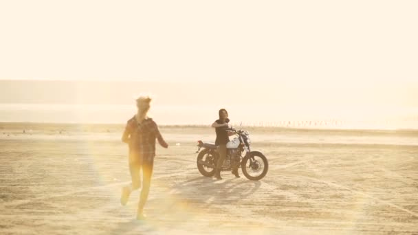 Atraktivní mladá žena motocyklista se svou přítelkyní na motocyklu v poušti na východ nebo západ slunce. Přítelkyně na kole. Ženy jezdec. Zpomalený pohyb