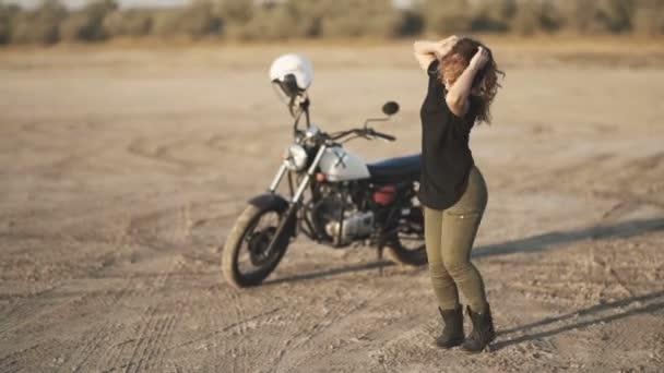 Mladá krásná žena tance v poušti při západu slunce nebo východu slunce. Motocykl na pozadí