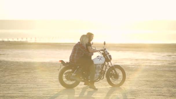krásná mladá žena motocyklista se svou přítelkyní na motocyklu v poušti na východ nebo západ slunce. Přítelkyně na kole. Zpomalený pohyb