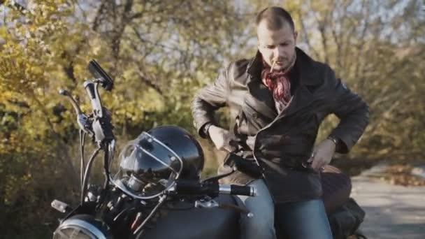 mladý muž motocyklista kouří cigaretu při posezení na motorce