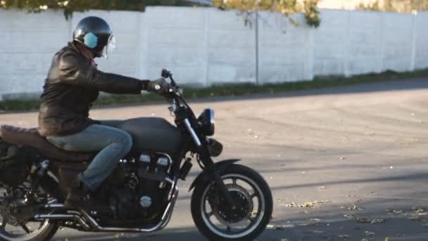 Muž na koni starý motocykl vlastní café-racer na venkovské silnici na podzimní slunečný den