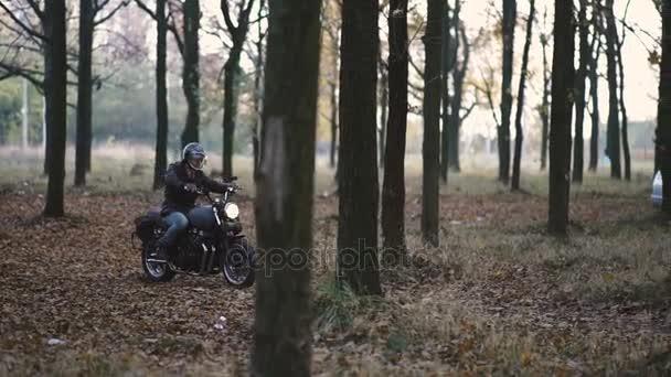 Muž na koni starý motocykl vlastní café-racer na lesní silnici při západu slunce