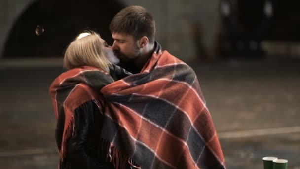 A young couple hug and kiss each other in a city Park at autumn cold night